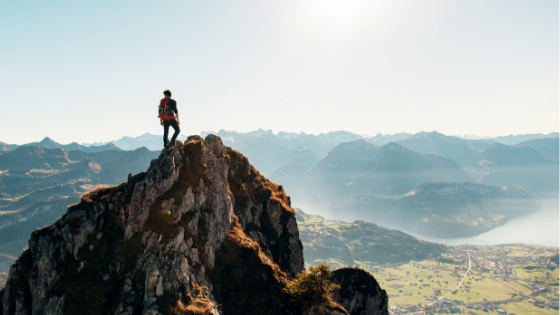 A man standing on top of the mountain - Supermom Global