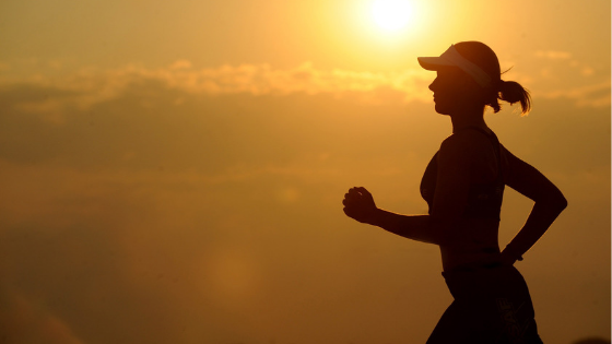 A woman jogging in a sunset background - Supermom Global