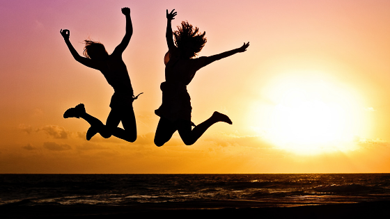 A two women on a jumpshot in a sunset background - Supermom Global
