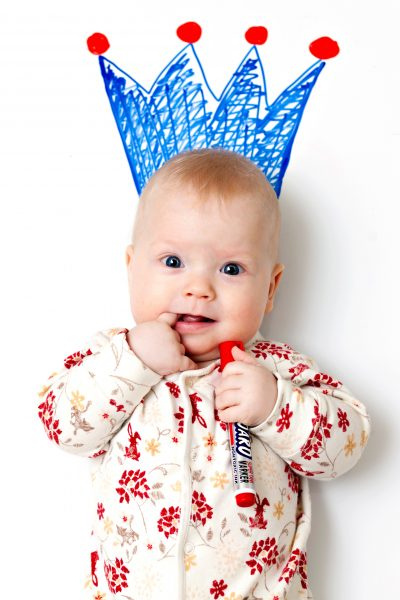 A baby boy smiling while holding a marker - Asian Trendy Mums SuperMomGobal