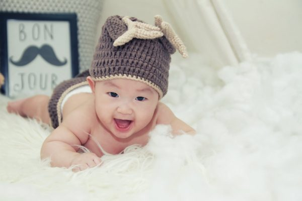 A baby boy wearing a bonnet while smiling - Asian Trendy Mums SupermomGlobal
