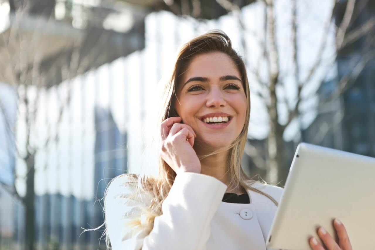 A girl smiling while holding a phone - Career and Entrepreneurship SupermomGlobal