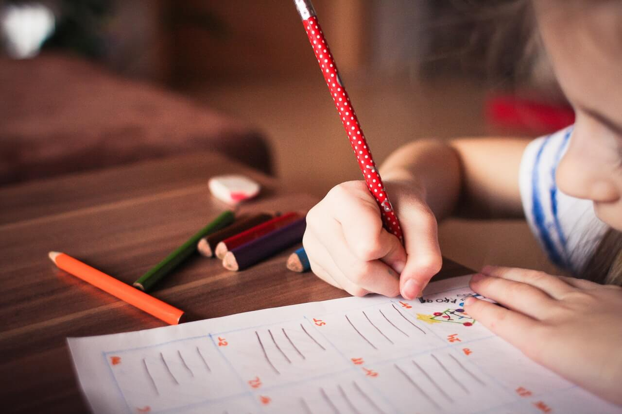 The girl is drawing using a red pencil - Childhood Education SupermomGlobal
