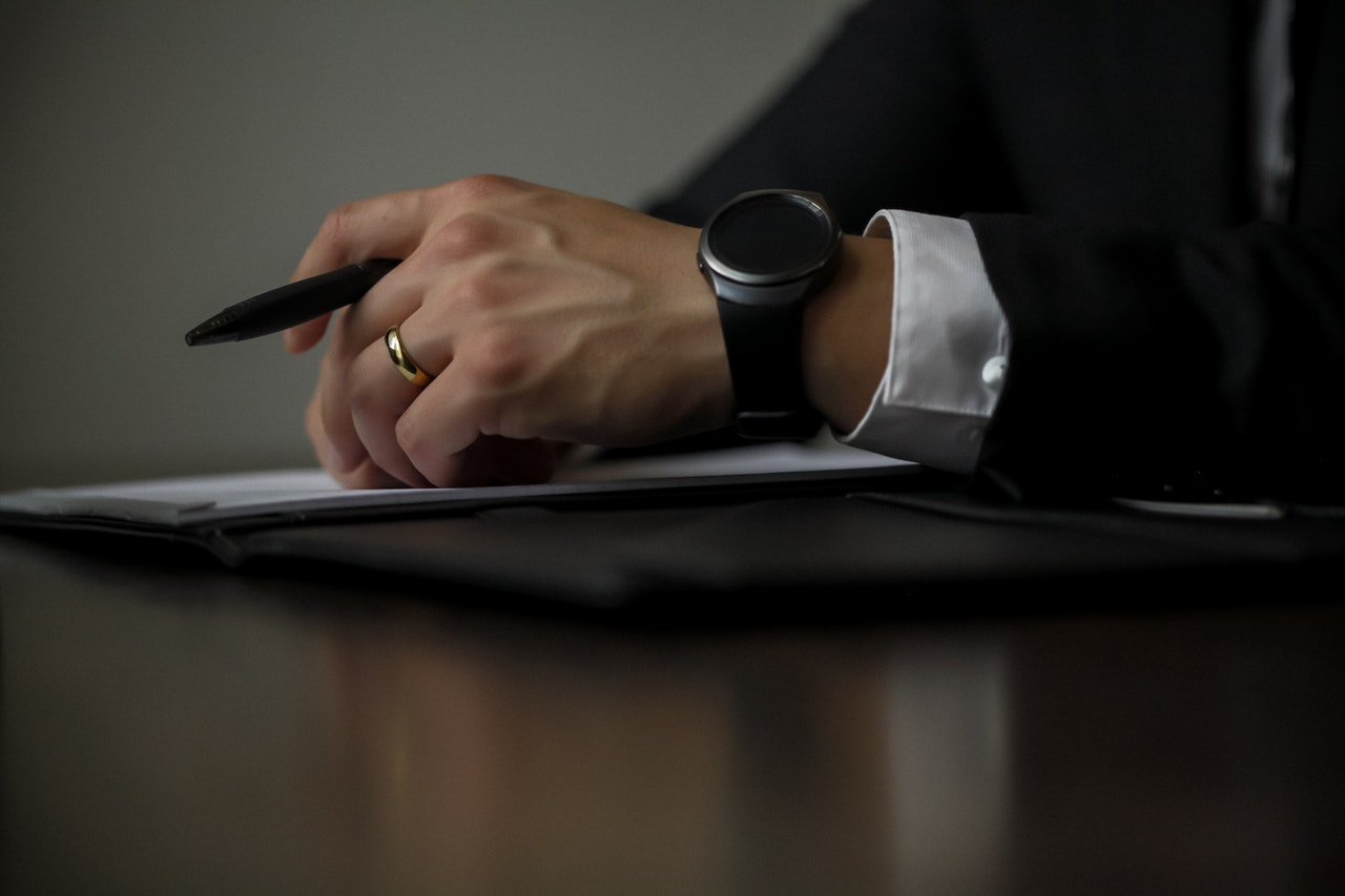A Man's wrist with a black pen and watch - Legal Matter SupermomGlobal
