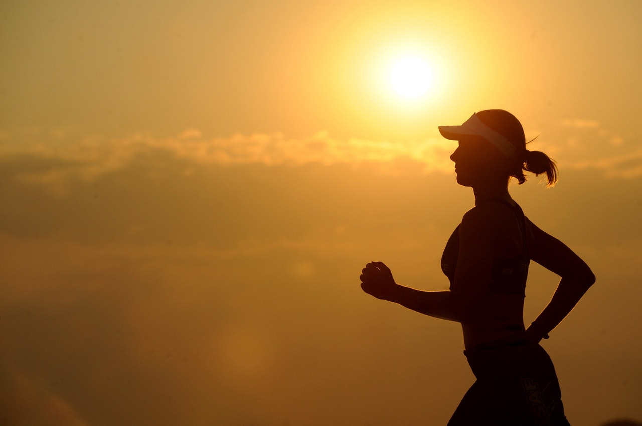 A silhouette jogging woman in a background sunset - Cosmopolitan Lifestyle SuperMomGlobal